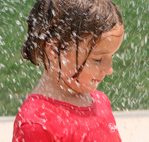 small girl in sprinkler