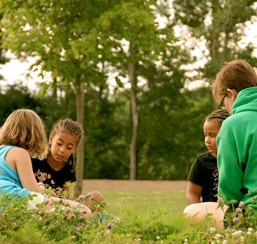 children talking while sitting in field
